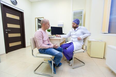 Baldness treatment. Patient suffering from hair loss in consultation with a doctor. Preparation for hair transplant surgery. The line marking the growth of hair. The patient controls the marking in the mirror Фото со стока - 124791766