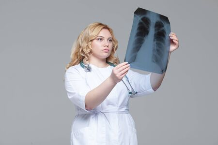 Young female doctor looking at the x-ray picture of lungs Фото со стока - 124791798