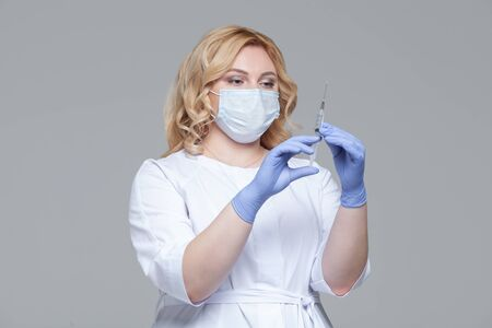 Female doctor in face mask holding syringe. Portrait of young woman doctor or nurse in protective gloves holding an injection