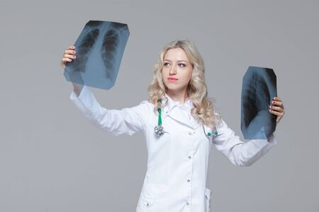 Young female doctor looking at the x-ray picture of lungs Фото со стока