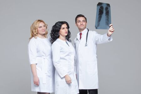 Young doctors looking at the x-ray picture of lungs Фото со стока - 124791807