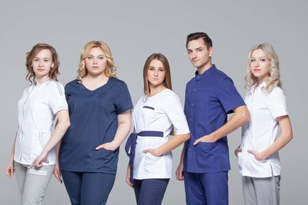 Successful team of medical doctors are looking at camera while standing on grey background Фото со стока - 124791805