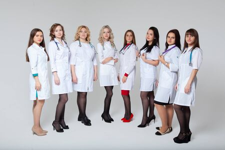Full length portrait of a successful group of doctors staying in front of grey background