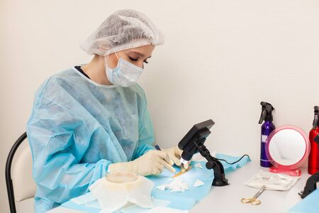 The doctor under the microscope recalculates the hair follicles. Baldness treatment. Hair transplant. Surgeons in the operating room carry out hair transplant surgery. Surgical technique that moves hair follicles from a part of the head. Фото со стока - 124795253