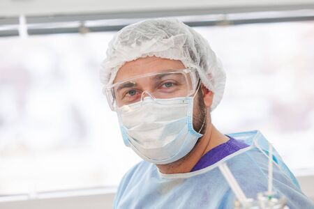 Portrait of surgeon. Baldness treatment. Hair transplant. Surgeons in the operating room carry out hair transplant surgery. Surgical technique that moves hair follicles from a part of the head. Фото со стока - 124795259