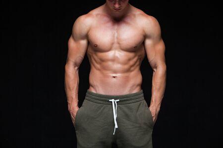 Hombre atlético fuerte - modelo de la aptitud que muestra su cuerpo perfecto aislado sobre fondo negro con copyspace. Hombre culturista con abdominales perfectos, hombros, bíceps, tríceps y pecho. Foto de archivo