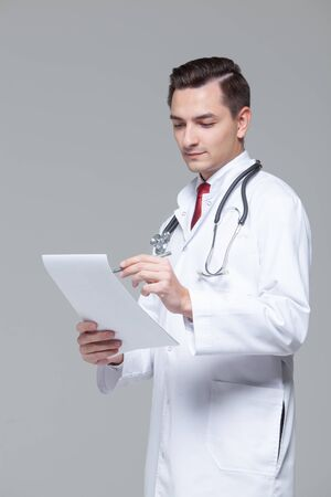 Portrait of young doctor in white uniform with stethoscope holding folder Archivio Fotografico