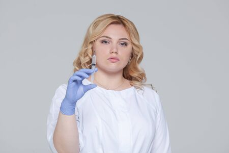 Portrait of young woman doctor or nurse in protective gloves holding an injection