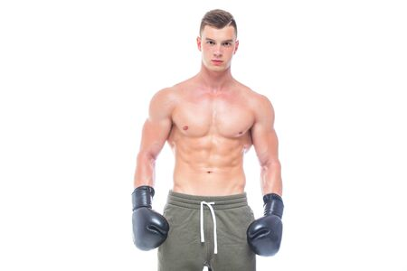 Muscular young man in black boxing gloves and shorts shows the different movements and strikes in the studio on a white background. Strong Athletic Man - Fitness Model showing his perfect body. Copy Space.