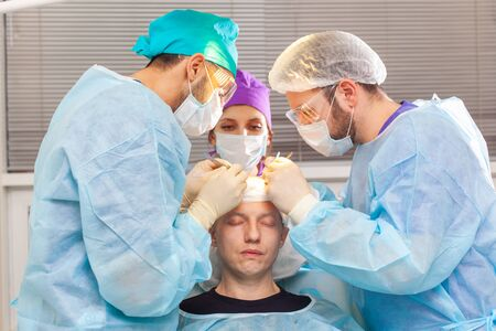 Baldness treatment. Hair transplant. Surgeons in the operating room carry out hair transplant surgery. Surgical technique that moves hair follicles from a part of the head. Фото со стока