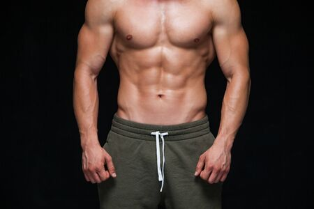 Strong Athletic Man - Fitness Model showing his perfect body isolated on black background with copyspace. Bodybuilder man with perfect abs, shoulders,biceps, triceps and chest.