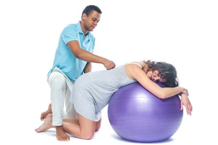 A young black man helps his white wife with birth pain with a ball. Partnered birth, partnered delivery. Isolated white background. Standard-Bild