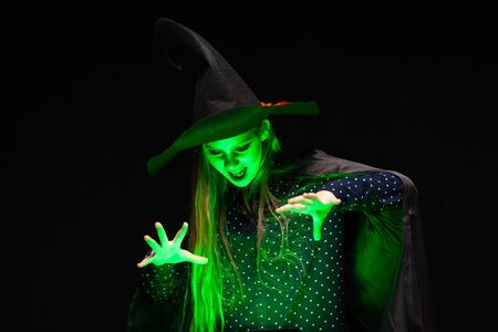 Halloween Witch over a pot of green glowing liquid conjures hands on black background. Beautiful young surprised woman in witches hat and costume . Wide Halloween party art design. Copy-paste. Witch craft concept. Stok Fotoğraf