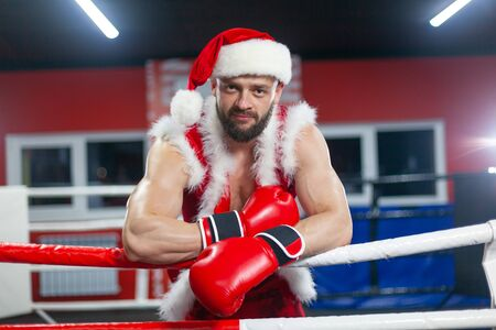 Christmas. A handsome muscular man in a Santa Claus suit with Boxing gloves stands in the ring. GYM.