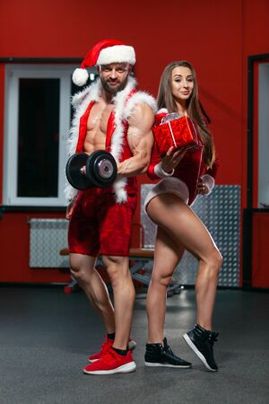 Christmas. Handsome muscular man in Santa Claus suit with dumbbells and fitness woman in red suit with gift . GYM. Stock Photo