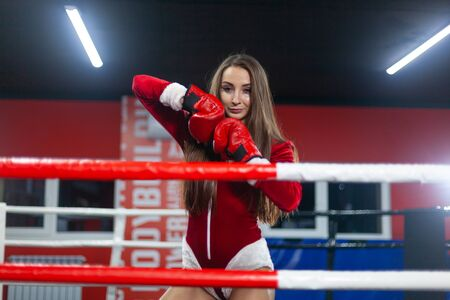 Christmas. A beautiful muscular woman in a Santa Claus costume with Boxing gloves stands in the ring. GYM.