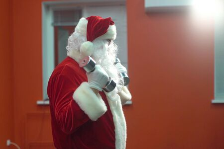 Santa Claus training at the gym on Christmas Day. Santa Claus is working out with dumbbells.
