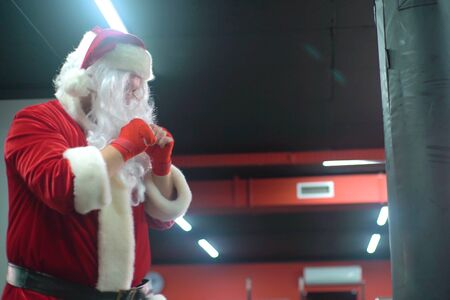 Santa Claus Fighter kickbox With Red Bandages boxer hitting a huge punching bag at a boxing studio. Santa Claus boxer training hard. Stock Photo