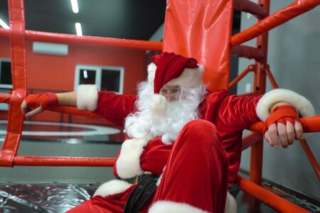 Santa Claus Fighter kickbox With Red Bandages boxer in the ring. Santa Claus boxer training hard