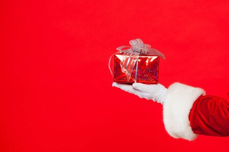 Photo of Santa Claus gloved hand with giftbox, on a red background. Christmas