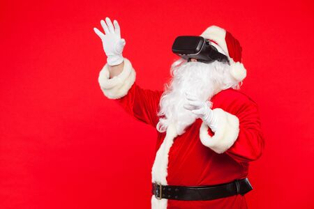 Santa Claus wearing virtual reality goggles, on a red background. Christmas Stok Fotoğraf