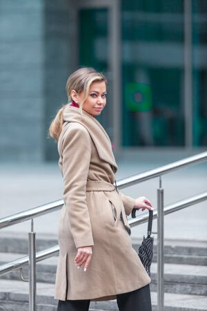 Outdoors lifestyle fashion portrait of stunning brunette girl. Walking on the city street. Going shopping. Wearing stylish white fitted coat, red neckscarf, black umbrella cane. Business woman.