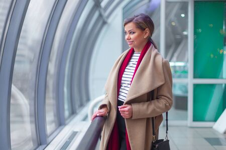 Outdoors lifestyle fashion portrait of stunning brunette girl. Walking on the city street. Going shopping. Wearing stylish white fitted coat, red neckscarf, black umbrella cane. Business woman. Black