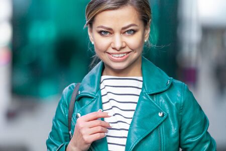Outdoors lifestyle fashion portrait of stunning brunette girl. Walking on the city street. Going shopping. Dressed in a stylish turquoise green jacket. Close up. Business woman.