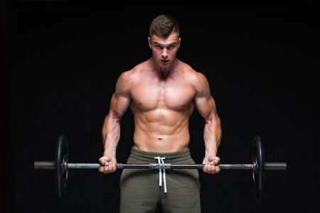 Muscular man working out in studio doing exercises with barbell at biceps, strong male naked torso abs. Isolated on black background. Copy Space. Strong tension. Sweat. Scream.