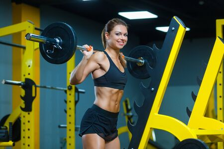 Photo of a smiling woman holding weight while working out with barbell in a gym. Muscles woman showing sixpack abs.
