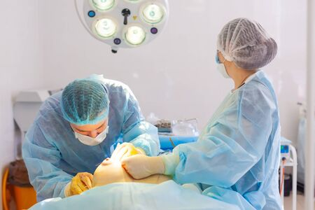 Hospital. Surgeon operates in the operating room. The surgeon places a suture on the breast after inserting the implant during breast augmentation surgery.