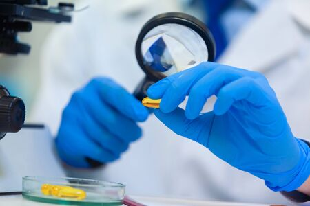 Scientist studies properties and benefits of omega 3 fatty acids using microscope and laboratory equipment in a medical laboratory Stock Photo