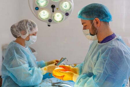 Hospital. Surgeon operates in the operating room. The doctor and nurse disinfect the implant before inserting it during breast augmentation surgery. 스톡 콘텐츠