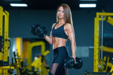 Slim athletic woman pumping up muscles with dumbbells in the gym. Front view. Muscles woman showing sixpack abs.