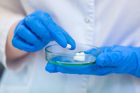 Tecnico che tiene la capsula di Petri con le pillole. Gli scienziati creano nuovi farmaci e vaccini in un moderno laboratorio scientifico