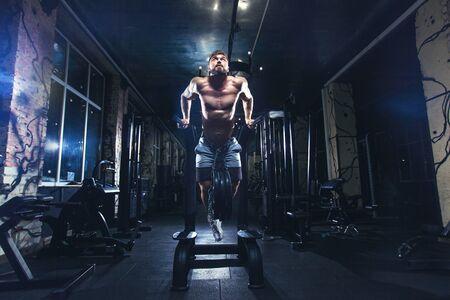 Muskularny mężczyzna trenuje na siłowni, robi pompki na drążkach, trenuje triceps. Nagi tors ABS Zdjęcie Seryjne