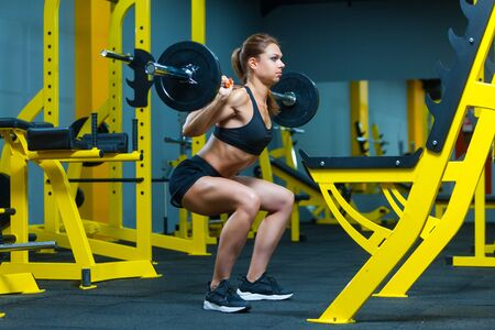 Side view of a young fitness woman doing barbell squats in a gym.