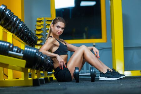 Young sporty woman sitting on the floor near a shelf with dumbbells in a gym. Side view