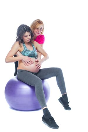 Young pregnant woman exercising with physiotherapist in birthing school. Doctors help conceptat in antenatal class. Isolated white background. 免版税图像