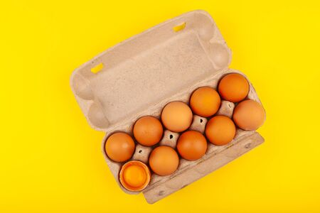 Egg Chicken eggs. Top view of an open gray box with brown eggs Isolated on a yellow background. One egg is half broken, yellow round yolk. The concept of a healthy lifestyle, getting pure protein. Proper Breakfast. Preparing for Easter.
