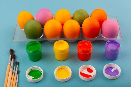 Colorful handmade Easter eggs and jars of multicolored gouache with tassels.. Top view of an open transparent box. Isolated on a blue background. Preparing for Easter