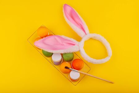 Colorful handmade Easter eggs, rabbit ears to play with, and jars of multicolored gouache with tassels.. Top view of an open transparent box. Isolated on a yellow background. Preparing for Easter
