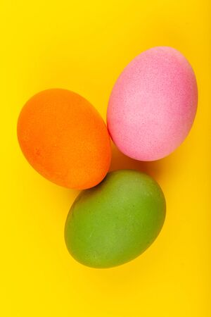 Colorful handmade Easter eggs. Top view of three eggs. Isolated on a yellow background. Preparing for Easter