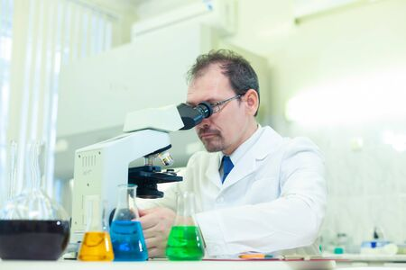 Chemist crazy. A mad scientist conducts experiments in a scientific laboratory. Performs research using a microscope.