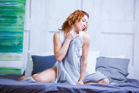 Photo of a girl holding a blue plaid sitting on the bed in the morning