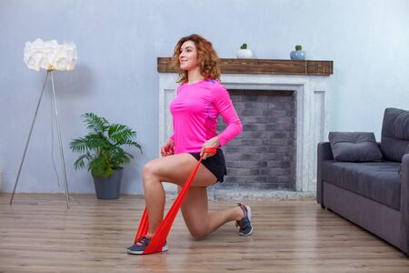 Side view of a girl in pink and black sportswear staying on one knee doing exercise with rubber bands at home