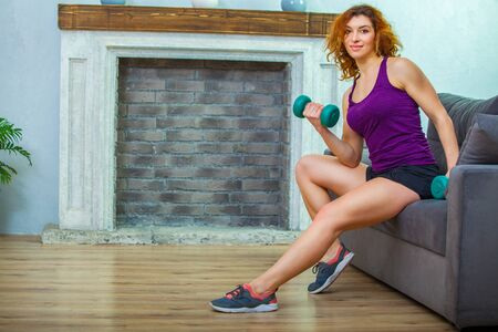Young woman is sitting on the edge of the sofa and lifting blue dumbbells doing morning exercises Zdjęcie Seryjne