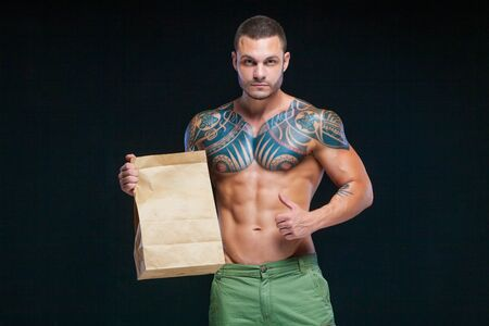 Muscular man bodybuilder with tattoos. Man posing on a black background with paper bag. The concept of advertising the right sports food. Copy paste logo.