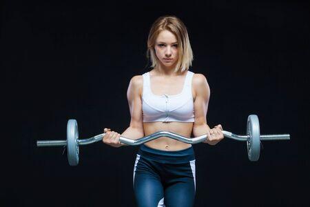 Retrato de primer plano de una chica joven muscular fitness posando con barra rizada en el gimnasio aislado sobre un fondo negro