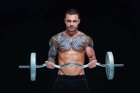 Tattooed strong muscular athletic man pumping up muscles with barbell on black background